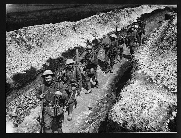 (6) Folio 19450 - Troops in steel helmets moving along a communication trench fully equipped for their various duties