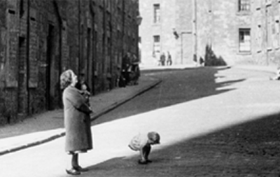 Film still of woman and children in street